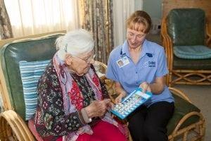 Registered Nurse assisting a DVA Community Nursing Program Client with webster pack