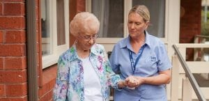 Carer and client walking at home