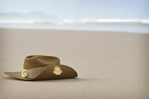 A close up of an Australian army slouch hat sitting on the sand of a beach