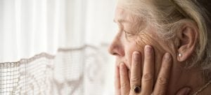 Portrait of sad lonely pensive old senior woman sitting near the window in her house looking out a window