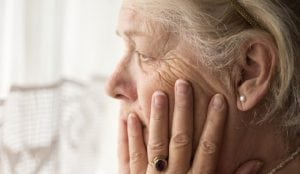 Portrait of sad lonely pensive old senior woman sitting near the window in her house looking out a window,