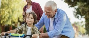 Caring for elderly parents, grandfather teaching grandson to ride a bike