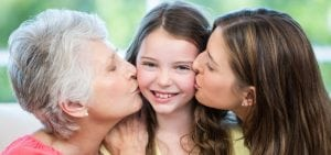 Home Care, Close-up of mother and grandmother kissing happy girl on sofa at home